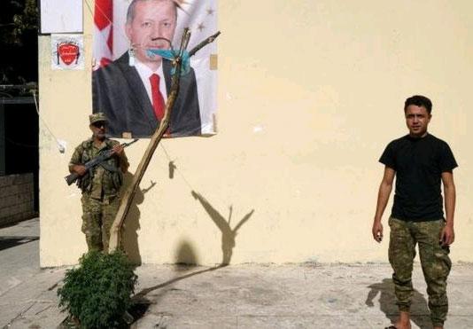 Cerablus'ta bir ÖSO üyesi, Erdoğan'ın posteri önünde fotoğraf çektiriyor.
